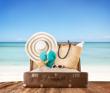 Concept of summer travelling with old suitcase and accessories  Blur beach on background photo