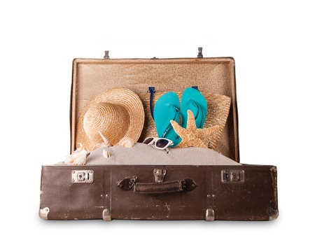 Isolated shot of retro suitcase with accessories on beach photo