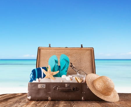 Concept of summer travelling with old suitcase and accessories Blur beach on background