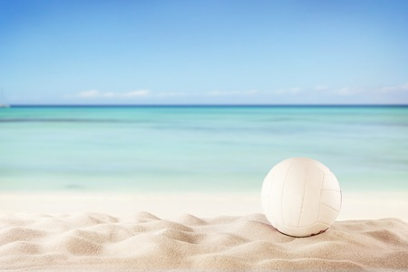 beach volleyball: Concept of beach volleyball with ball on sand, blur sea as background Stock Photo
