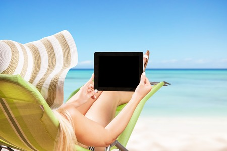 Concept with girl holding tablet in hands, blur tropical sandy beach on background photo