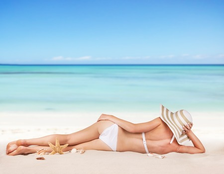 beautiful legs: Young blond woman relaxing on beach, blur sea as background