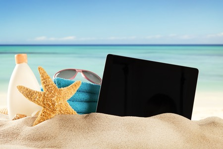 Concept with summer beach, tablet and accessories, blur sea on background photo