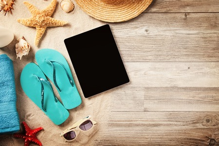 Top view of summer accessories and blank tablet on wooden planks photo