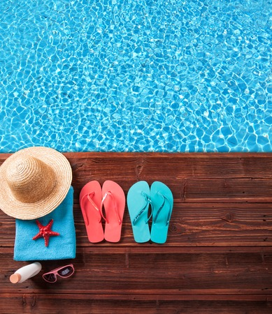 pool deck: Concept of summer accessories on wood with blue water