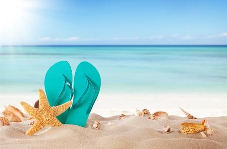 砂浜のビーチ、貝殻や青のサンダルで夏の概念 写真素材