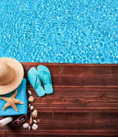 towel beach: Concept of summer accessories on wood with blue water as background Stock Photo