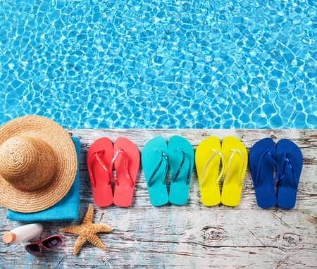 Concept of summer accessories on wood with blue water as background Stock fotó