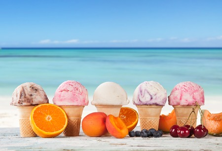 Set of various kind of fruit ice cream on wooden deck with blur sea on background photo