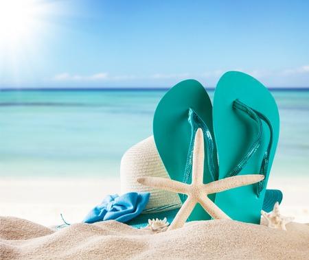 Zomer concept met zandstrand, schelpen en blauwe sandalen