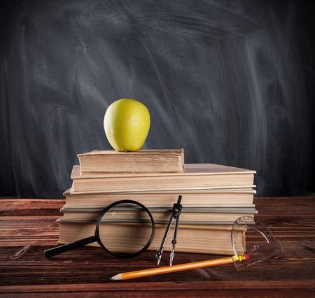 Still life of school tools and books with blackboard on background photo