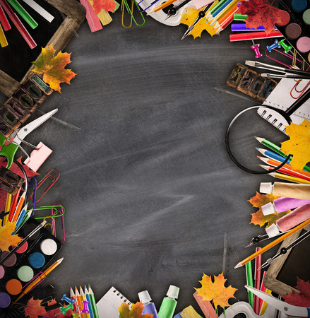 school life: Still life of school tools and books with blackboard on background Stock Photo