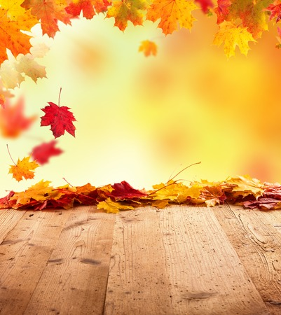 Moody autumn background with falling leaves on wooden planks photo
