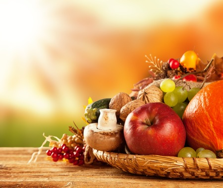 harvest: Autumn concept of traditional food  Mix of pumpkins, fruit and vegetable on wooden table with blur background  Free space for text