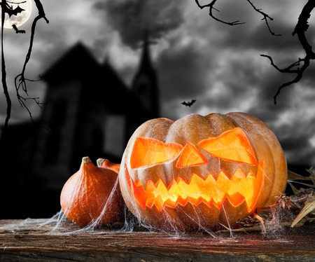 Concept of halloween pumpkin on wooden planks  Blur scary castle on background photo