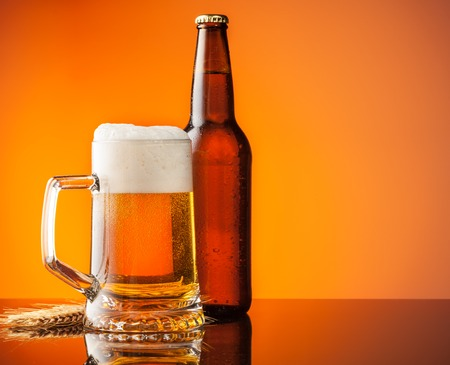 cool backgrounds: Glass with bottle of beer with blur orange background