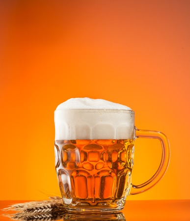 Glass of beer with blur orange background photo