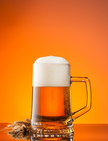 wheat beer: Glass of beer with blur orange background