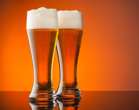 foam party: Glasses of beer with blur orange background