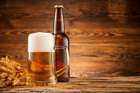 beer pint: Glass and bottle of beer with wheat ears on wooden planks Stock Photo