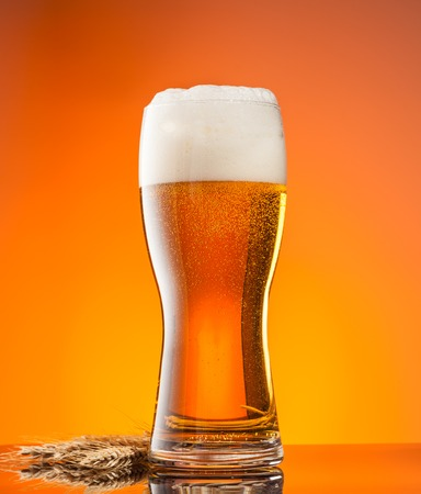 amber light: Glass of beer with blur orange background