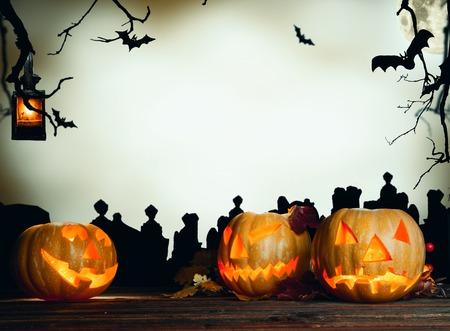 horror background: Concept of halloween pumpkin on wooden planks. Cemetery grave stones on background