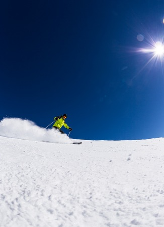 Alpine skier skiing downhill, blue sky on background Reklamní fotografie