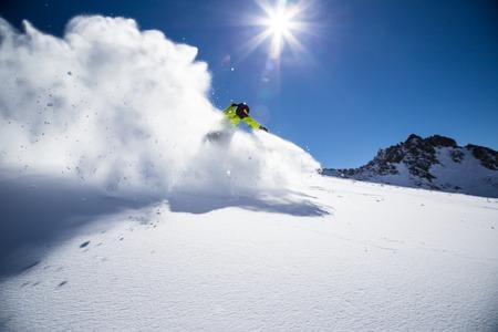 Alpine skier skiing downhill, blue sky on background Archivio Fotografico