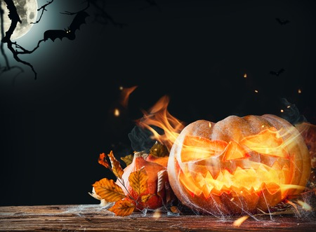 Halloween pumpkin with fire flames on wooden planks. Shinning moon on background photo