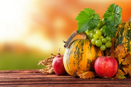 harvest background: Seasonal harvested agriculture products on wooden planks with blur background