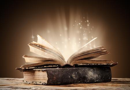 magico: Libros viejos en tablones de madera con fondo borroso brillo Foto de archivo
