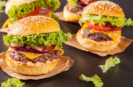 tasty beef burgers on wooden table photo