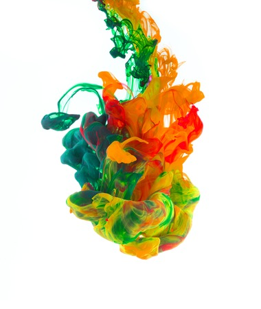 Studio shot of colored ink in water, isolated on white background Imagens