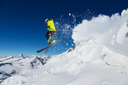 Alpine skier skiing downhill, blue sky on background Imagens
