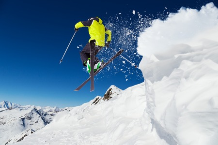 Alpine skier skiing downhill, blue sky on background photo
