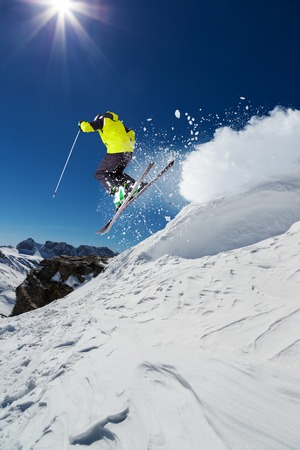 Alpine skier skiing downhill, blue sky on background Zdjęcie Seryjne