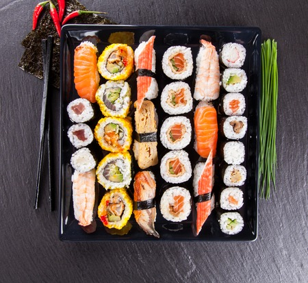 Various kinds of sushi food served on black stone