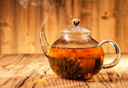 tea kettle: Teapot with blooming tea on wooden planks