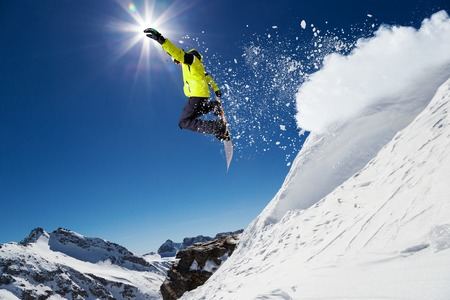 fly: Alpine skier skiing downhill, blue sky on background Stock Photo