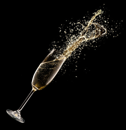 Celebration theme. Glass of champagne with splash, isolated on black background Stock Photo