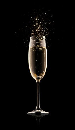 Celebration theme. Glass of champagne with splash, isolated on black background Imagens