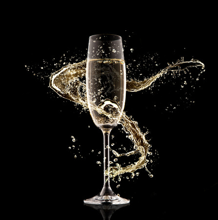 background black: Celebration theme. Glass of champagne with splash, isolated on black background Stock Photo