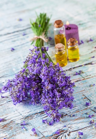 Lavender blossoms on wood with oil glass bottles photo