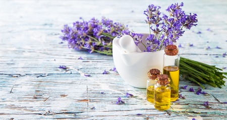 Lavendelbos met olie en zeep op wit hout Stockfoto