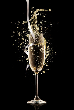Celebration theme. Glass of champagne with splash, isolated on black background Stock Photo - 33012592