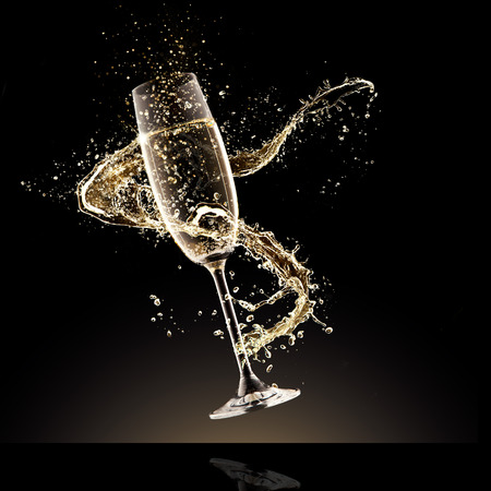 champagne bubbles: Celebration theme. Glass of champagne with splash, isolated on black background Stock Photo