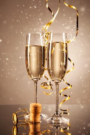 リボンと周りの泡シャンパンのグラス。お祝いの概念