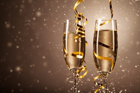 Glasses of champagne with ribbons and bubbles around. Concept of celebration Stock Photo