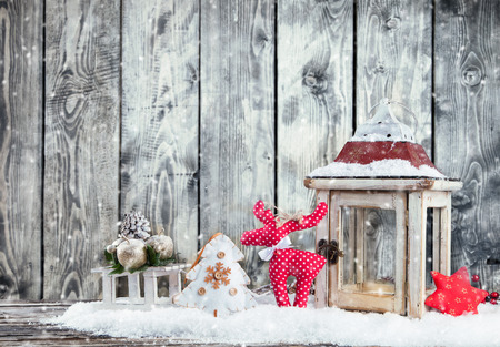 Christmas still life with lantern, gifts and caribou. Wooden planks as background photo