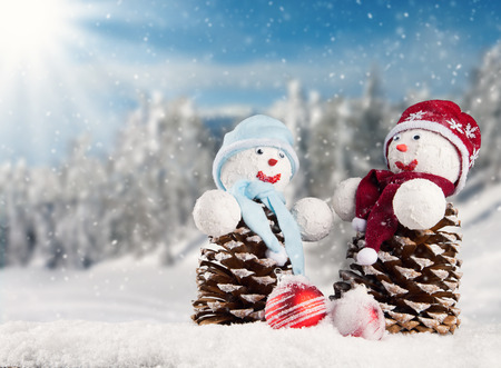 Winter holiday happy snow men with blur landscape on background. Concept love and togetherness photo